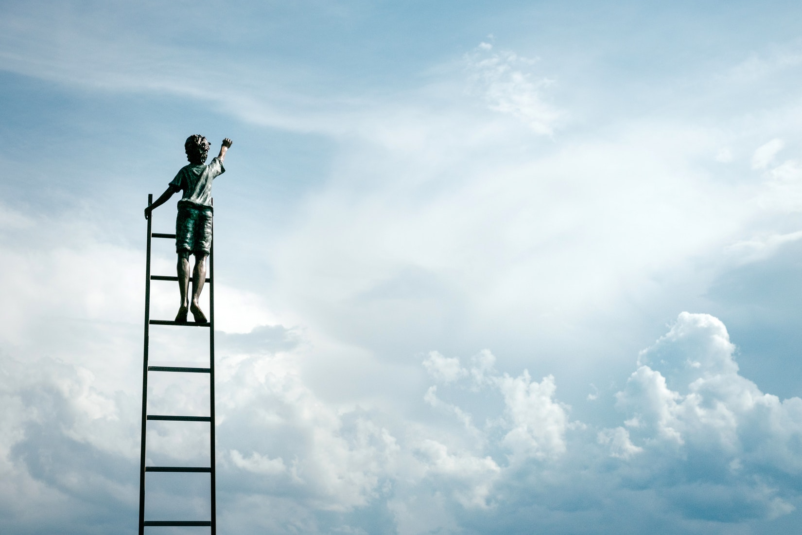 Child climbing a ladder stretching up into the sky